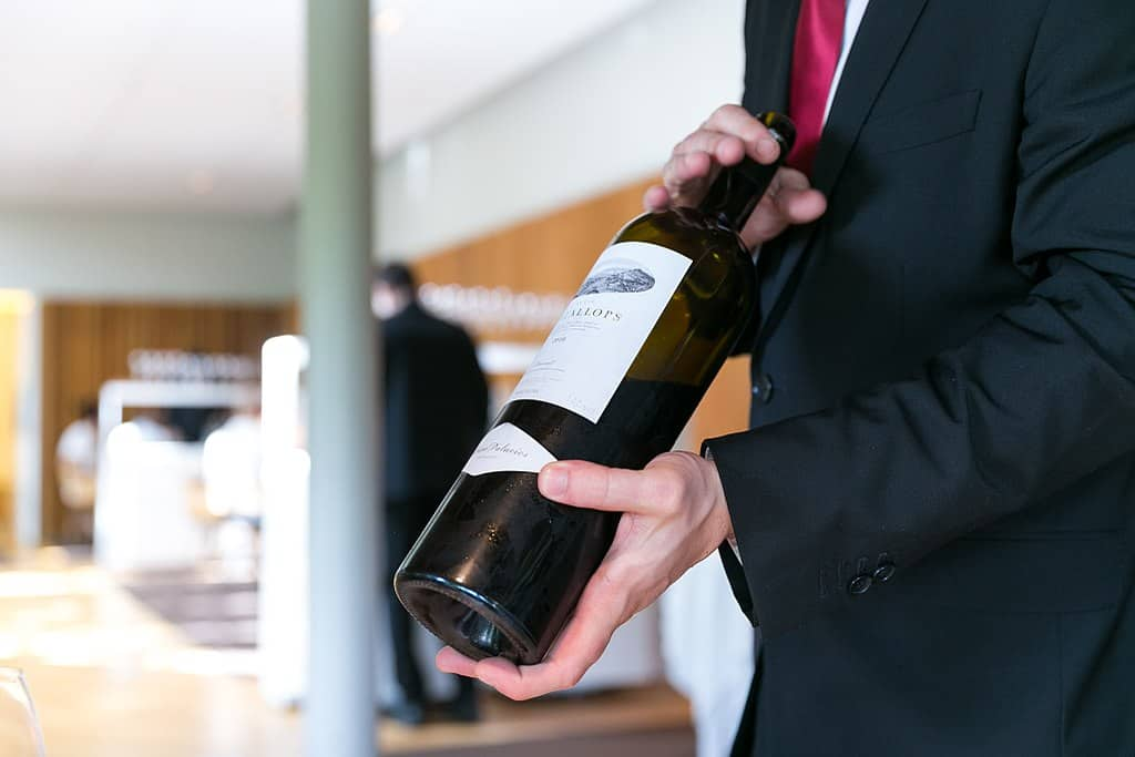A server displays a bottle of Priorat wine.